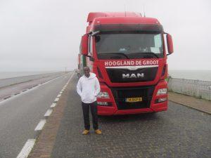 Samuel voor de vrachtwagen op de Afsluitdijk